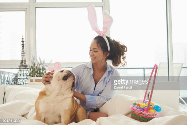 young woman on bed with dog - dog easter stock pictures, royalty-free photos & images