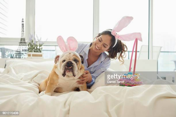 Young woman on bed with dog