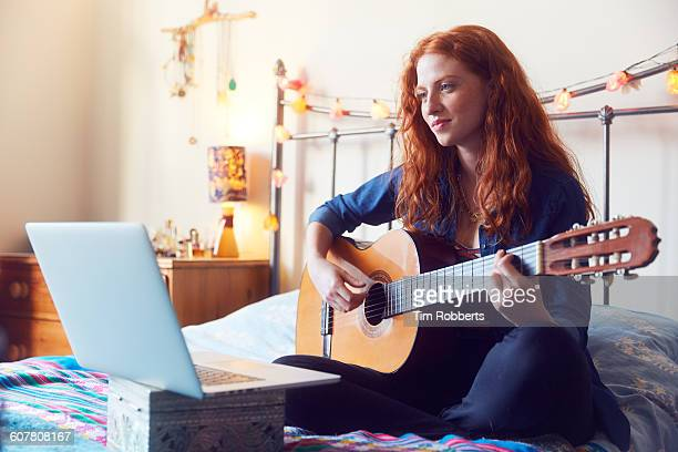 young woman on bed with guitar and laptop - gitarre stock-fotos und bilder