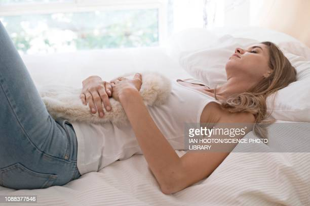 young woman on bed with hot water bottle on tummy - ciclo de menstruación fotografías e imágenes de stock