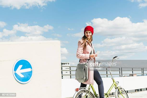 Young woman on bicycle holding cell phone