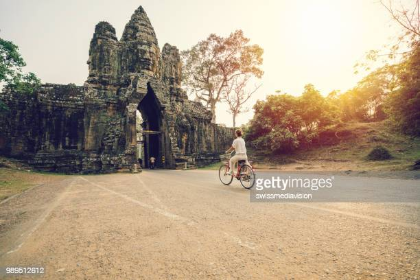 young woman on bicycle in ancient temple complex in cambodia - cambodia stock pictures, royalty-free photos & images