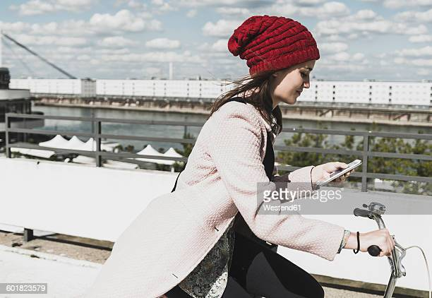 young woman on bicycle looking at cell phone - desaturated stock pictures, royalty-free photos & images