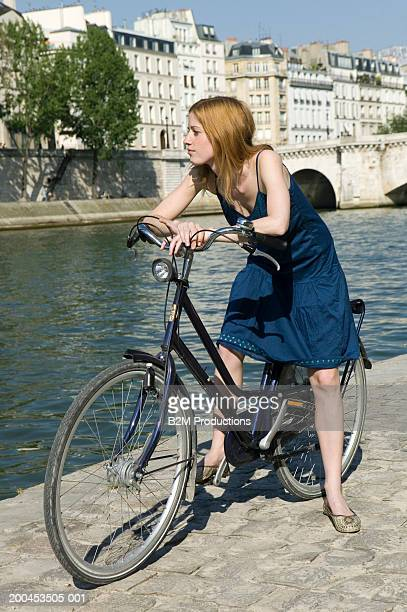 Young woman on bicycle, looking at river from quay