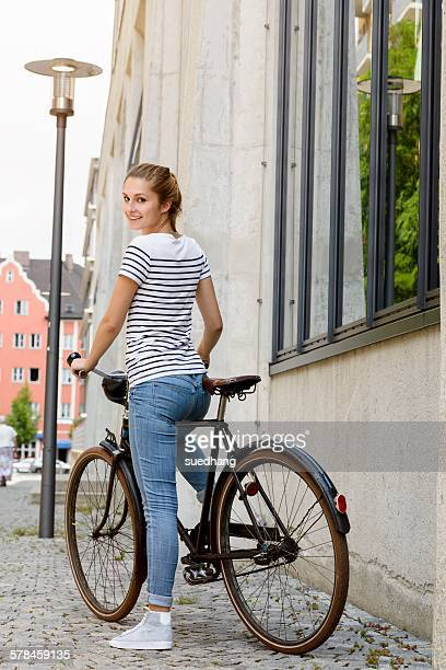 Young woman on bicycle looking over shoulder at camera smiling