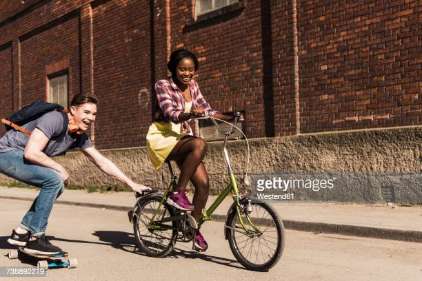 Young woman on bicycle pulling young man, standing on skateboard
