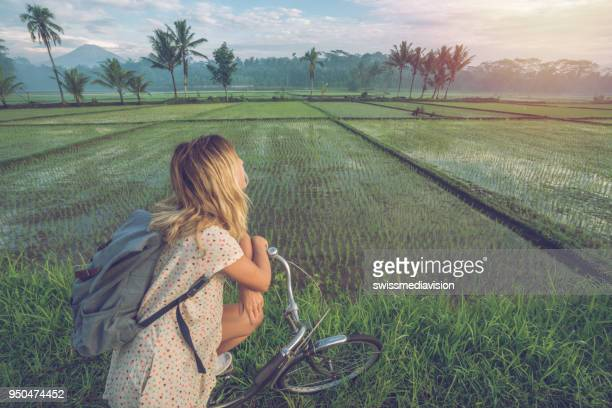 young woman on bicycle stops to admire rice fields, indonesia - indonesia photos stock photos and pictures