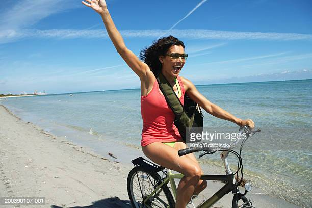 Young woman on bicycle waving, smiling, close-up