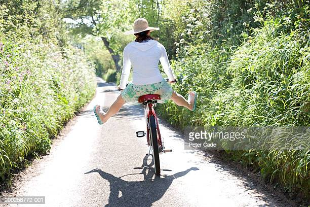 young woman on bicycle with legs spread open, rear view - woman leg spread stock photos and pictures