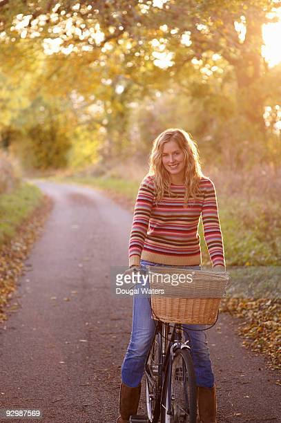 Young woman on bike in countryside.