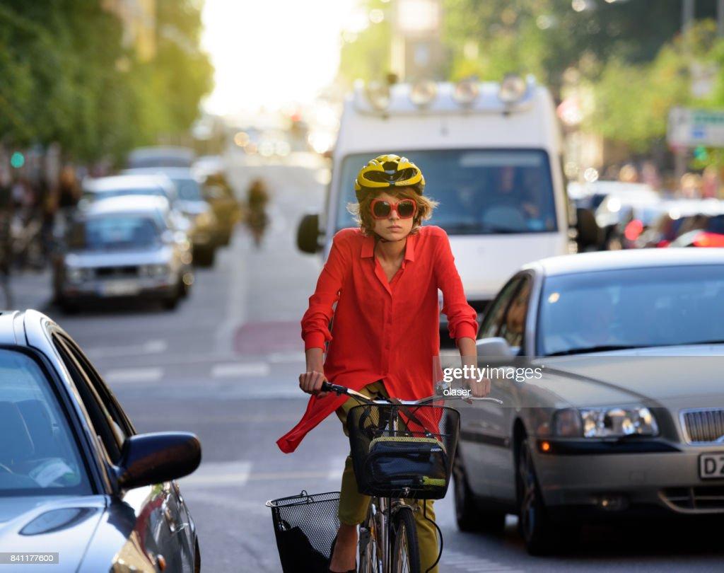 Young woman on bike, in traffic, dooring, danger : Stock Photo