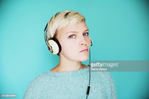 young woman on blue wearing headphones - rekha garton stock pictures, royalty-free photos & images