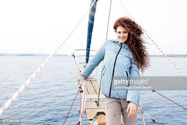 Young woman on bow of yacht