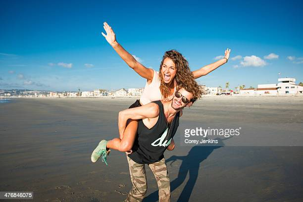 Young woman on boyfriend's back with arms raised