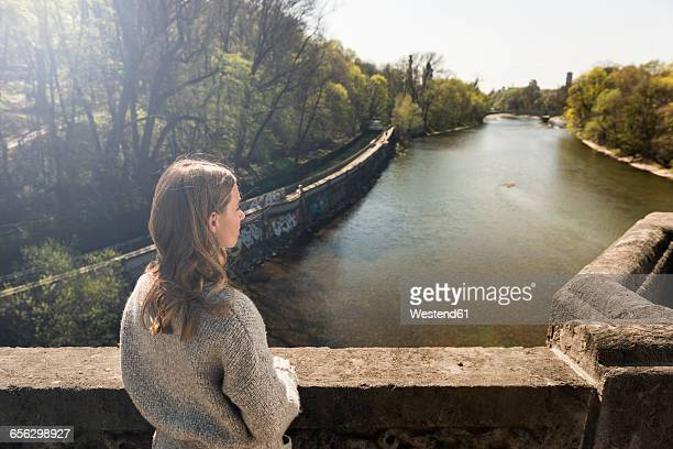 Young woman on bridge looking at river