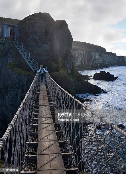 Young Woman On Carrick-a-Rede Rope Bridge in Northern Ireland