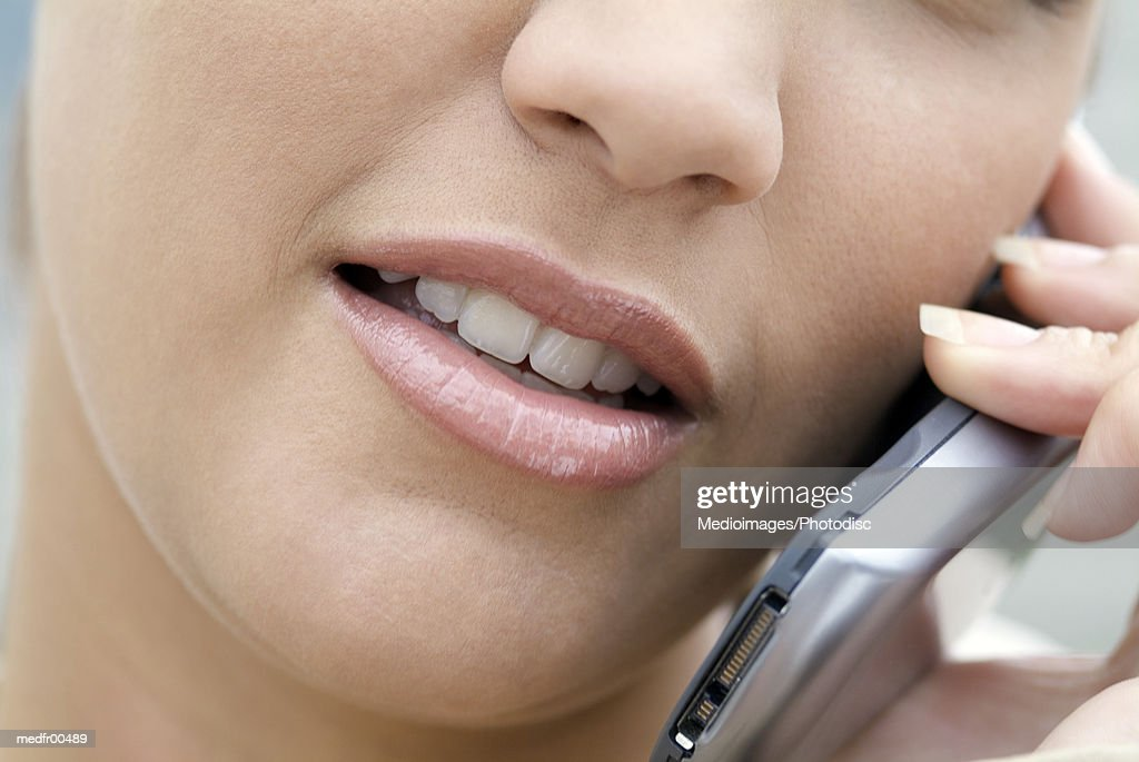 Young woman on cell phone, extreme close-up : Stock Photo