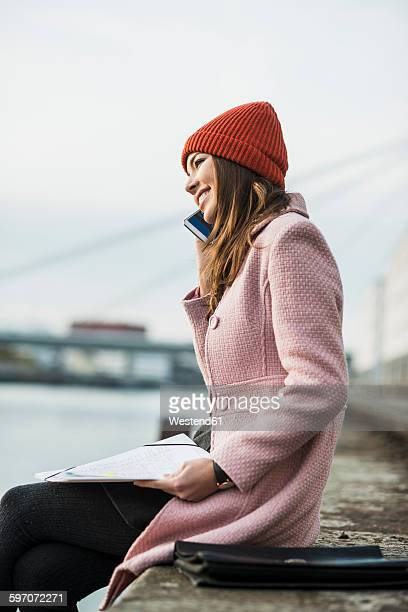 young woman on cell phone sitting at the riverside - kopfbedeckung stock-fotos und bilder