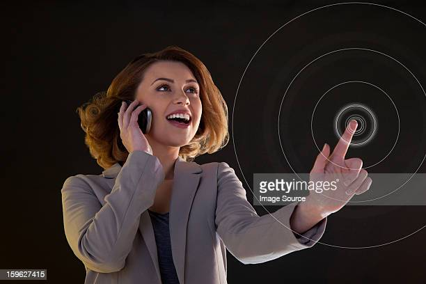 Young woman on cellphone and touching virtual circle