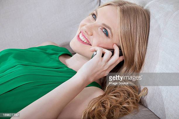 young woman on cellphone, lying on sofa - florence douillet photos et images de collection