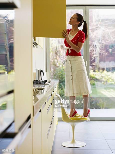 young woman on chair looking in cupboard - armadietto da cucina foto e immagini stock