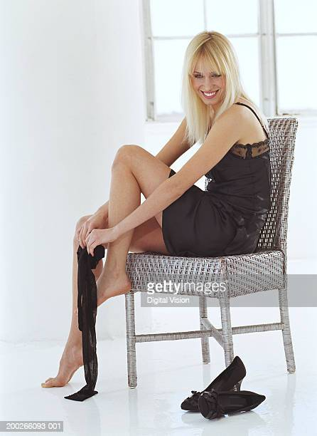 Young woman on chair putting on tights, smiling