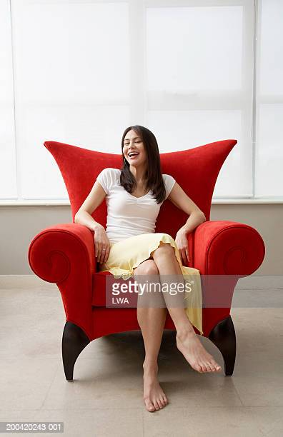 young woman on chair, smiling, portrait - white skirt stock pictures, royalty-free photos & images
