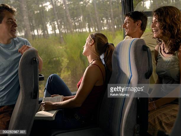 Young woman on coach wearing earphones in row between friends, smiling