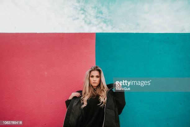 mujer joven en la pared colorida - coat fotografías e imágenes de stock