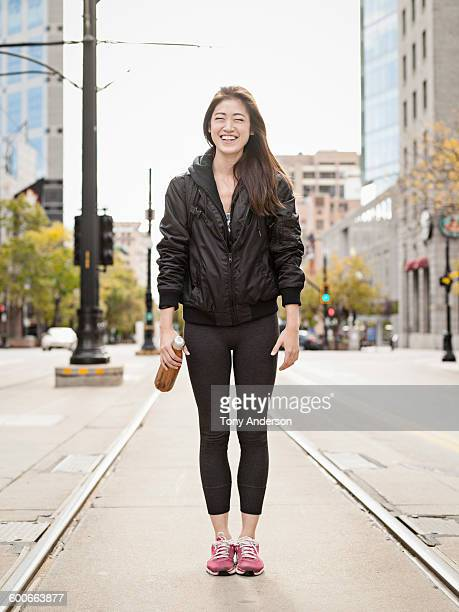 young woman on commuter tracks in city street - leggings stock pictures, royalty-free photos & images