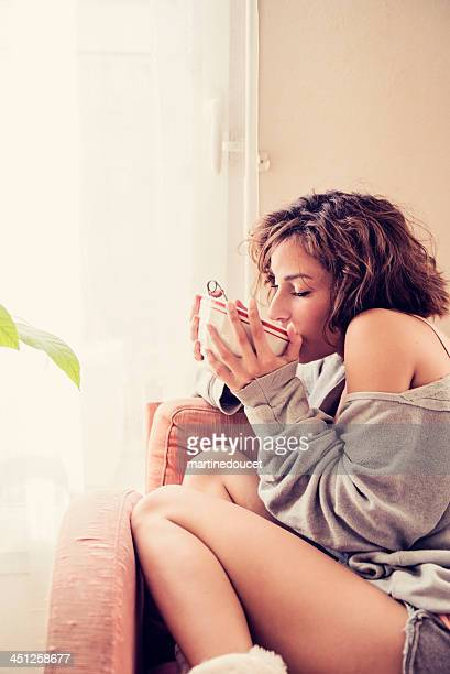 """young woman on cosy morning at home with tea bowl. - """"martine doucet"""" or martinedoucet stockfoto's en -beelden"""
