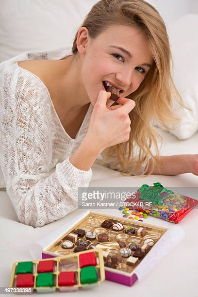 Young woman on couch nibbling sweets