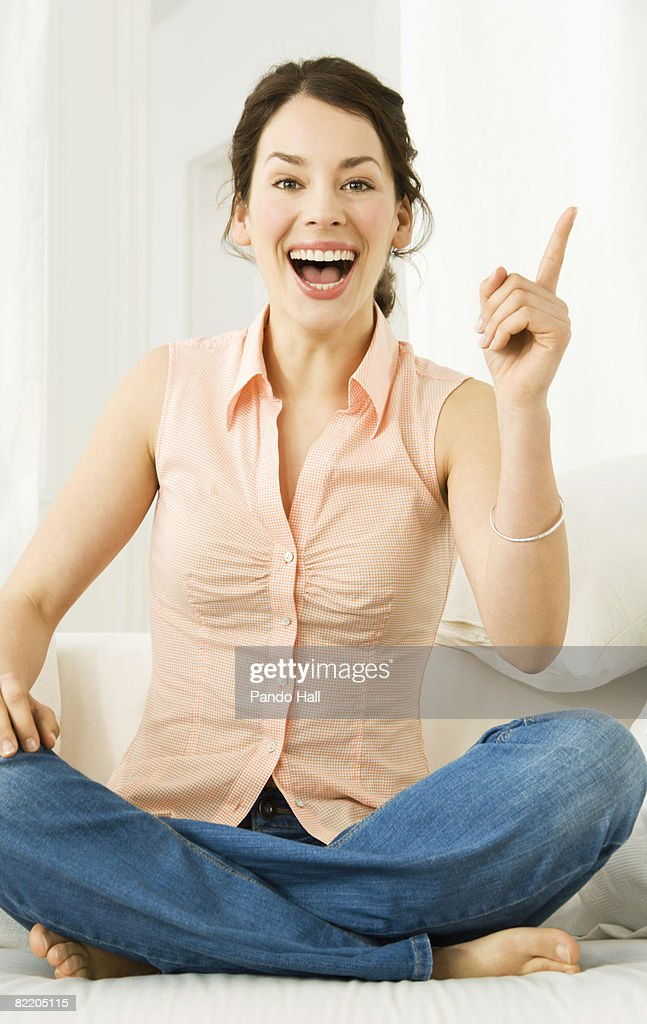 Young woman on couch pointing, laughing : Stock Photo