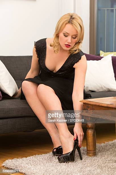 young woman on couch putting on high heeled shoes - beautiful women bent over stock photos and pictures