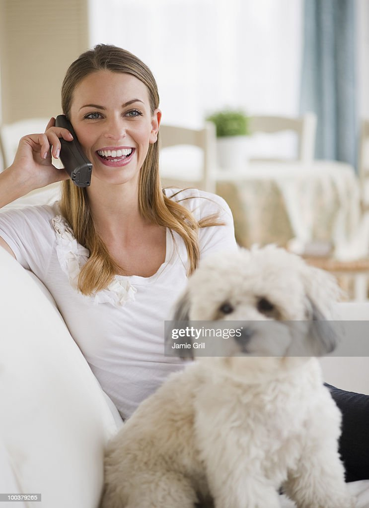 Young woman on couch with dog, talking on phone : Bildbanksbilder