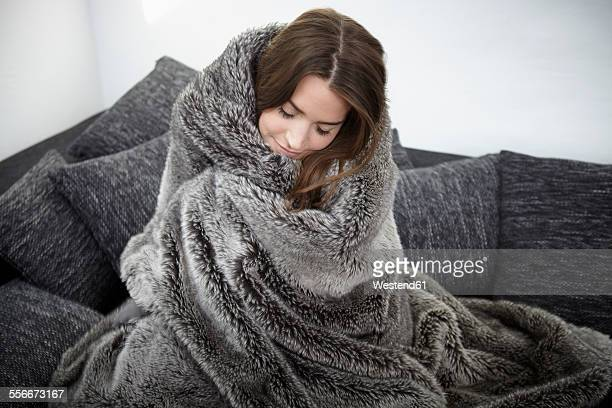 Young woman on couch wrapped in fur blanket