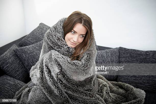 young woman on couch wrapped in fur blanket - avvolto foto e immagini stock