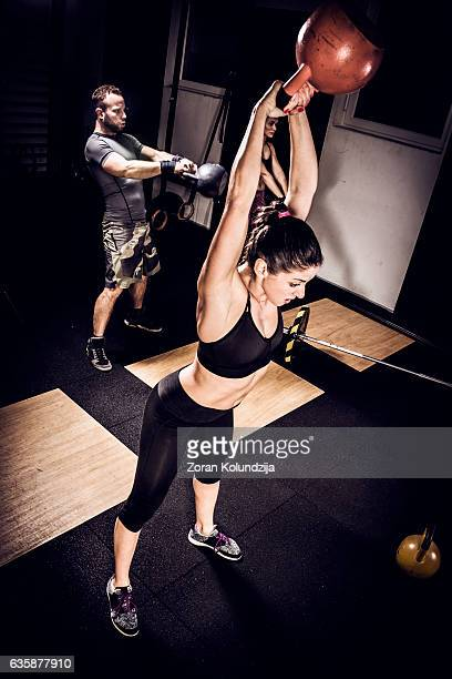 Young woman on cross training with kettlebell in gym