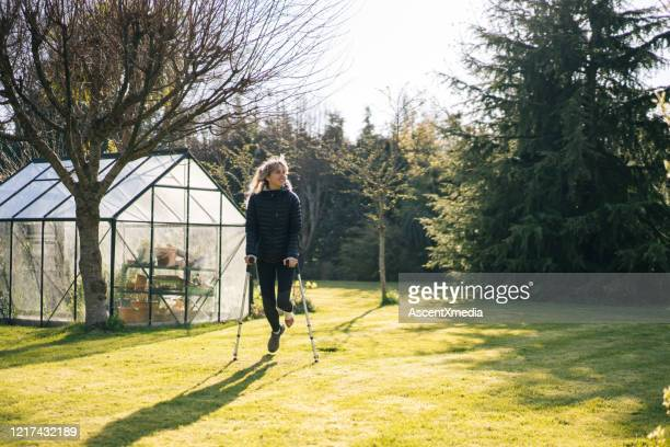 young woman on crutches relaxes in garden - green coat stock pictures, royalty-free photos & images
