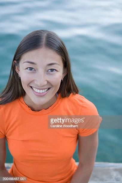 Young woman on dock, smiling, portrait, elevated view