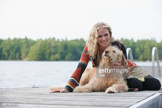 Young woman on dock with dog