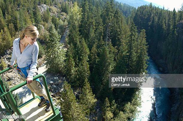 Young woman on edge of bungee platform, looking down, (wide angle)