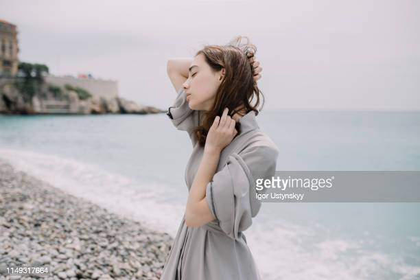 young woman on empty beach - 髪に手をやる ストックフォトと画像