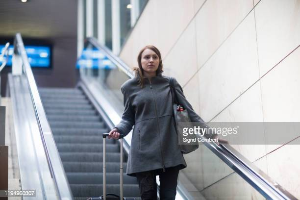 young woman on escalator in train terminal - sigrid gombert stock pictures, royalty-free photos & images