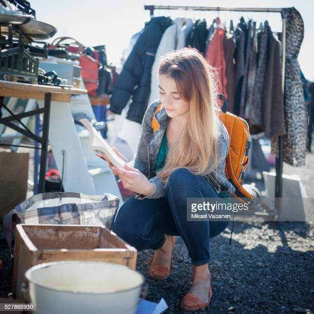 Young woman on flea market looking through displayed products