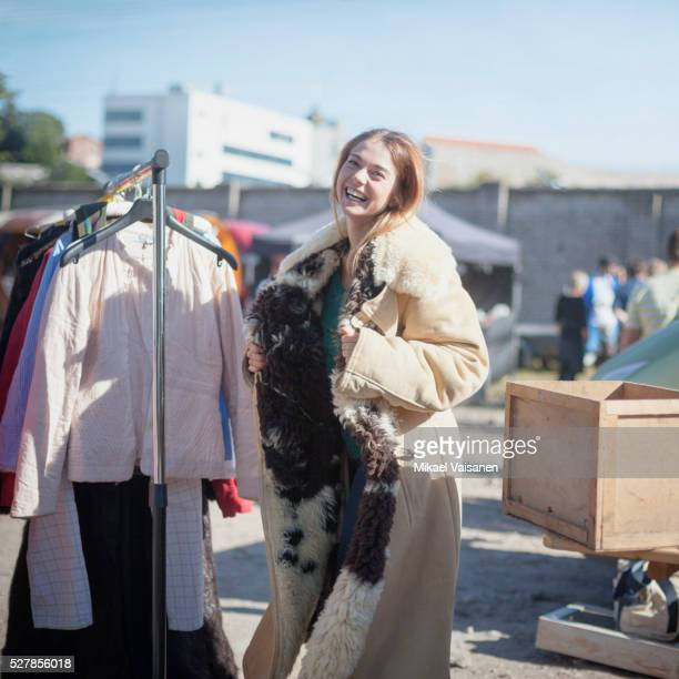Young woman on flea market trying on fur coat
