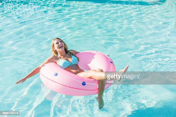 Young woman on float in swimming pool
