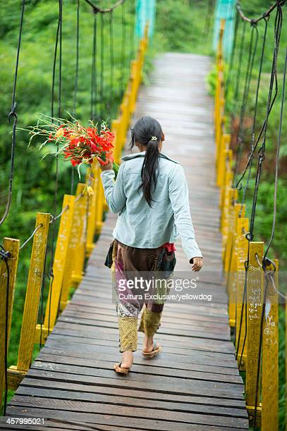 Young woman on footbridge with flowers, Shan State, Keng Tung, Burma