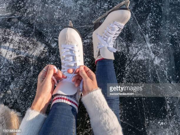 凍った湖の若い女性が日没時にアイススケートを着て、冬休みを楽しむ準備をしています - スケート靴 ストックフォトと画像