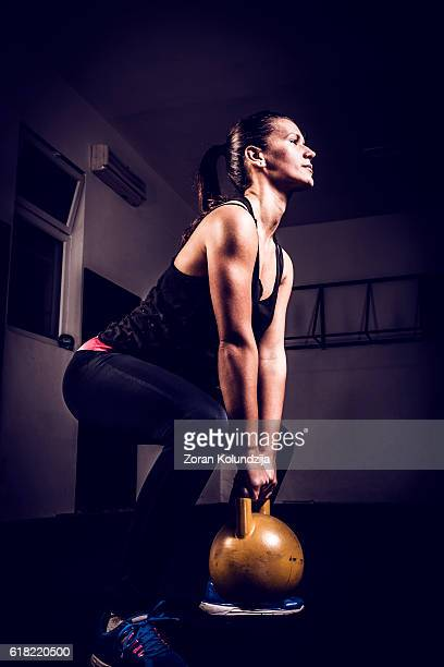 Young woman on gym training with kettlebell in gym